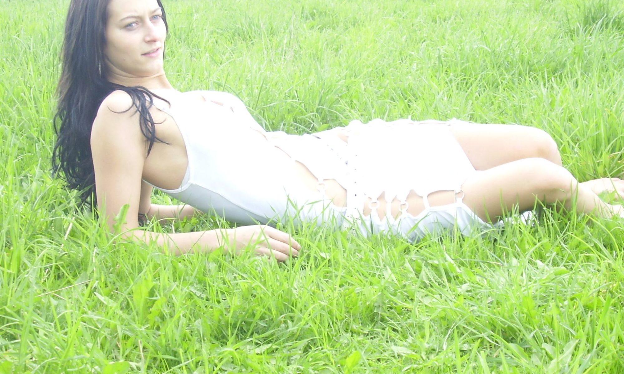 Schwarzhaarige Frau im weißen Kleid liegt auf der Wiese